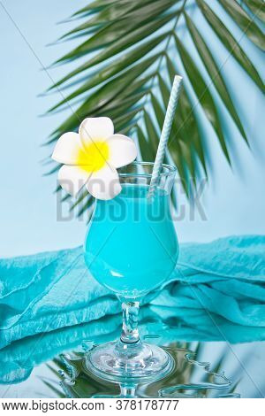 Exotic Tropical Blue Curacao Cocktail Drink In A Glass With Plumeria Frangipani Flower, Palm Leaf, F