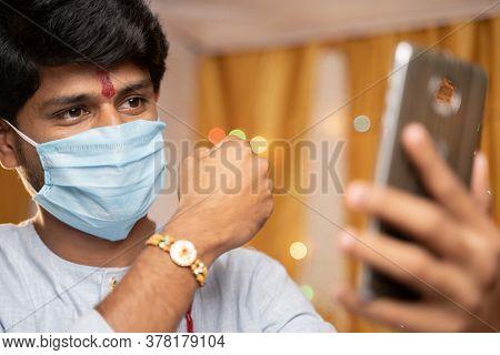 Man In Medical Mask Busy On Mobile Phone And Showing Rakhi Or Rakshabandhan To Sister Or Family Frie