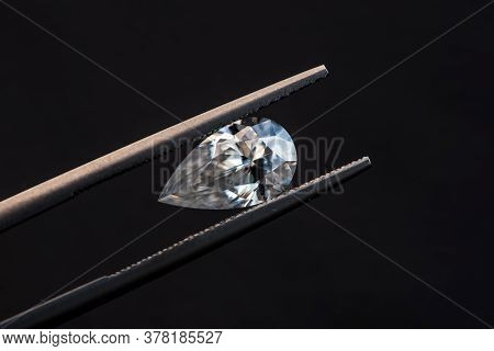 Pear Cut Diamond In Tweezers On The Black Background