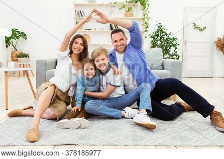 Family Housing. Happy Parents Joining Hands Making Symbolic Roof Above Their Children Sitting On Flo