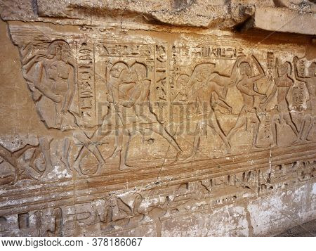 Pharaonic Sculptures Of Wrestling Sport And Hieroglyphs Carved On An Ancient Wall In Luxor, Egypt