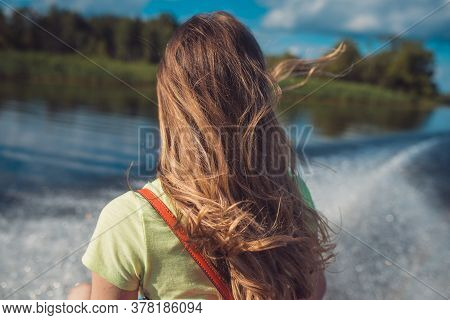 A Young Woman With Long Hair Rides A Fast Boat On The Water Surface Of The Lake. Back View. Against