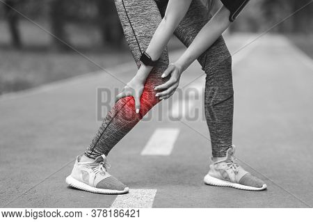 Sport Trauma. Female Jogger With Injured Calf Massaging Painful Leg Muscle With Red Sore Spot Suffer