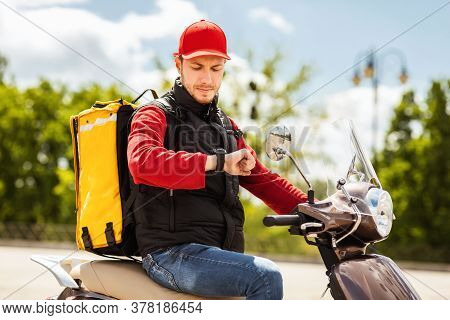 On-time Delivery Service. Courier Guy On Scooter Checking Time On Wristwatch Delivering Food In City
