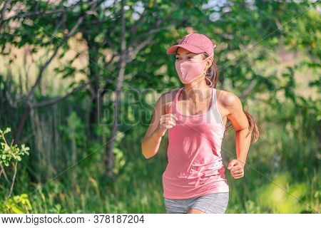 Mask wearing COVID-19 outdoor run exercise. Asian woman running outside with face covering while exercising jogging on run sport workout in summer park nature. Pink mask, cap, tank top.