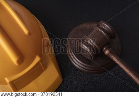 Yellow Safety Helmet And Judge Gavel. Construction Law. Close Up.