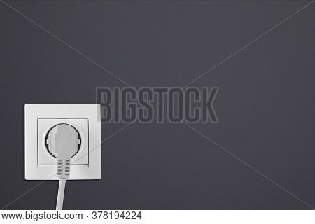 Dark Grey Wall With Power Socket And Inserted Plug, Space For Text. Electrical Supply