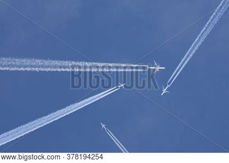 Passenger Planes Crossing With Chemtrails In A Blue Sky