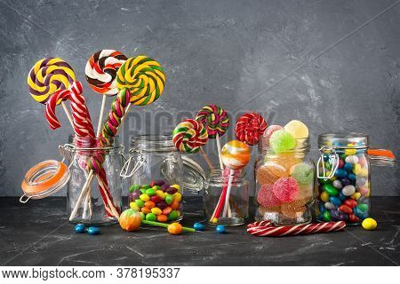 Colored Lollipops, Colorful Round Candies And Marmalade In Glass Jars On A Black Stone Table With A