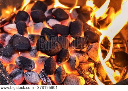 Top View Of Hot Flaming Charcoal Briquettes Glowing In The Bbq Grill Pit. Grill Briquettes That Are