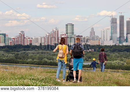Couple In With Baby Pram Walking On Top Of A Hill On Background Of Summer City And Buildings Under C