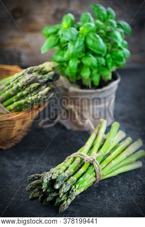 Asparagus. Fresh raw organic green Asparagus sprouts closeup. Over wooden table. Healthy vegetarian food. Raw vegetables, market. Healthy eating, diet, dieting concept. Vertical image