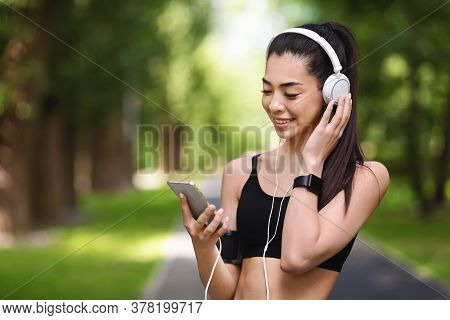 Music For Jogging. Sporty Asian Girl With Smartphone And Headphones Outdoors Choosing Songs For Her