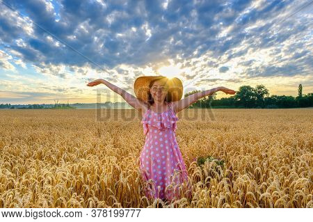 Smiling Woman In Straw Hat In Wheat Field With Outstretched Arms At Morning
