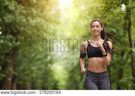 Active Lifestyle. Motivated Sporty Girl Jogging In Green Summer Park, Copy Space