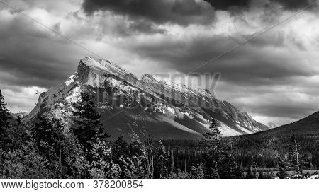 Black And White Photo Of Dark Clouds Hanging Over Mount Rundle In Banff National Park In The Canadia