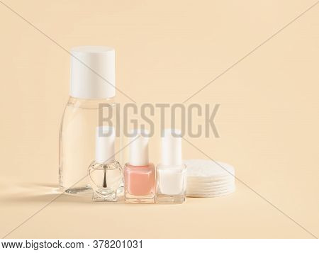 Nail Varnish Remover, White, Pale Pink And Colorless Nail Polish, Cotton Pads On A Powdery Color Bac