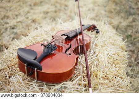 One Violin And Bow Placed On A Pile Of Straw In The Field. Music Violin Training