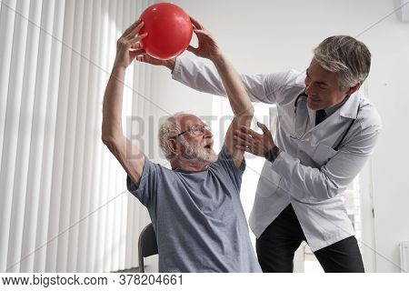 Experienced Doctor Doing Physical Exercises With Elderly Man