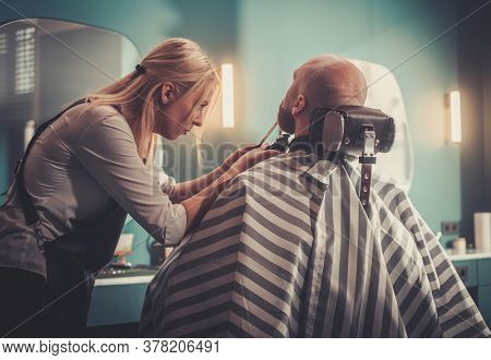 Professional Stylist is Focused to Make Trendy Beard Cut.