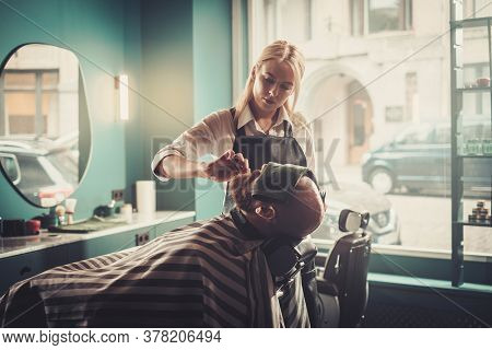 Hipster Man Sits on the Chair With Closed Eyes and a Towel During Professional Beard Cutting.