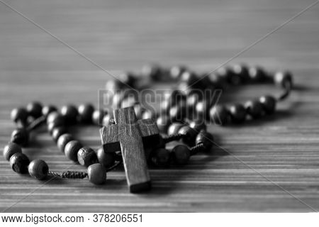 The Rosary. Close Up Of Wooden Rosary Beads With Jesus Christ Holy Cross Crucifix On The Table In Bl