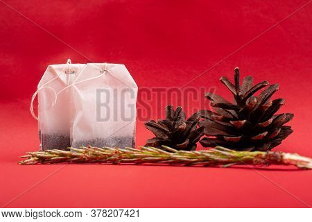 Tea Bags Close-up With Pine Cones And A Sprig Of Spruce On A Red Background. Forest Flavored Tea.