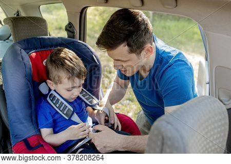 Close-up Shot Of Concentrated Father Helping His Son To Fasten Belt On Car Seat. Child Transportatio