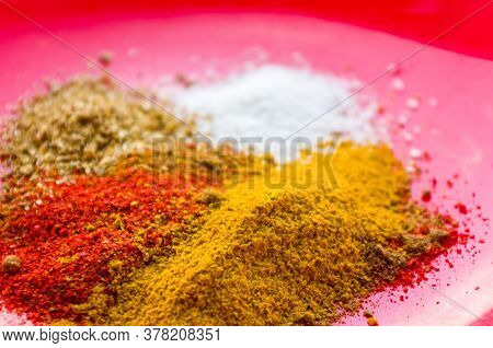 - Red Pepper, Ground Coriander, Salt And Turmeric On A Red Plate, Close-up