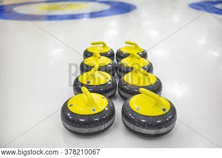 The Curling Stone Or Rock Is Made Of Granite With Yellow Handles Lie On The Ice, In The Background A