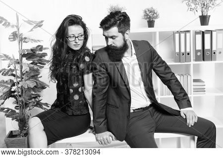 Running Business Together. Business Couple Sit On Office Desk. Sexy Woman And Bearded Man In Formalw