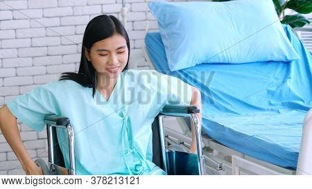 Young Happy Asian Woman On Wheelchair In A Hospital Ward . Medical Healthcare And Patient Treatment