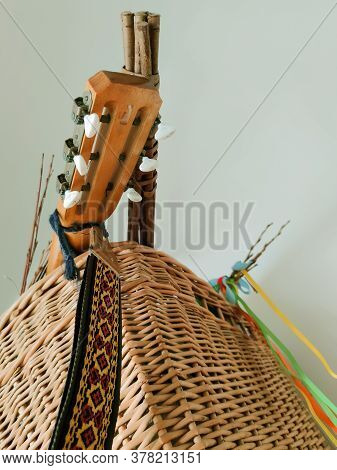 Wicker Basket, Brown Fretboard Of A Six String Wooden Guitar