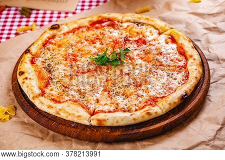 Italian Pizza Margherita With Tomatoes And Mozzarella Cheese On Wooden Cutting Board. Close Up