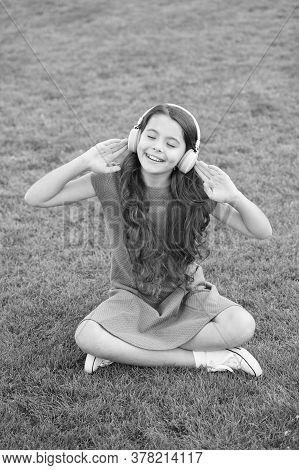 Educational Podcast. Girl Headphones Listening Music. Kid Girl Enjoy Music Green Grass Meadow. Pleas