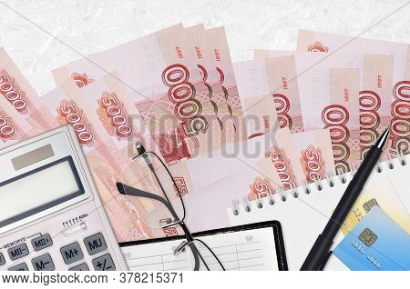 5000 Russian Rubles Bills And Calculator With Glasses And Pen. Tax Payment Concept Or Investment Sol