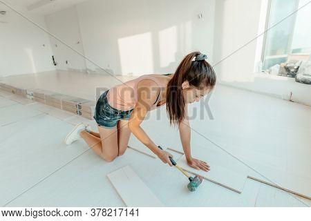 Engineered hardwood new floor installation in house remodeling woman installing wood flooring herself DIY project.