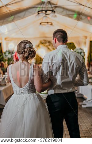 Back View Of Romantic Couple Of Bride And Groom On Banquet Hand In Hand. The Lights Of The Electric