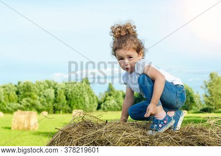 Little Beautiful Girl On The Field, On Roll Haystack. Child Plays During Haymaking. Childhood. Harve