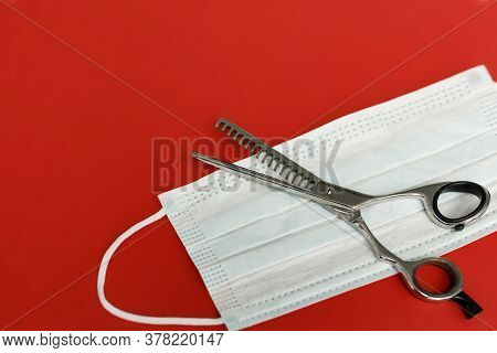 Hair Thinning Scissors And Medical Mask On A Red Background. The Concept Of Opening Beauty Salons Af