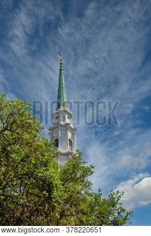 A Church Steeple Rising Into The Sky Beyond Trees