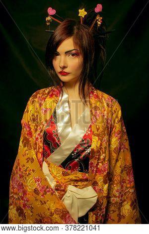Pretty Geisha In Kimono Posing Over Dark Background