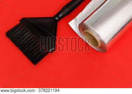 Black Brush And Foil Roll For Hair Coloring. Red Background.