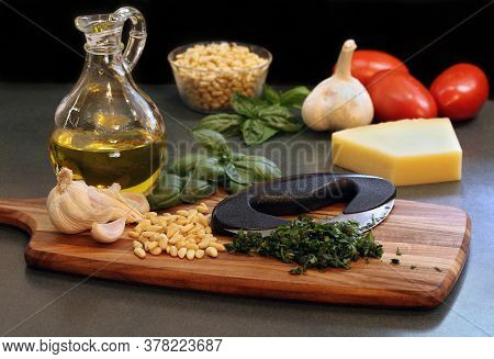 Chopped Basil On A Cutting Board With A Mezzaluna Knife And Ingredients To Make Pesto Sauce.