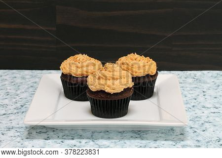 Three Chocolate Cupcakes With Swirled Peanut Butter Frosting.  Close Up With Copy Space.