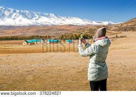 Autumn Nature Hiker Girl Walking In National Park In Altai, Russia. Woman Traveler Makes Photo With
