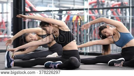 Group Of Sporty Young Asian Women In Sportswear Warming Up With Gymnastics And Stretching Exercises