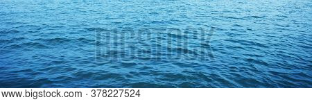Panoramic Sea Wave Picture. Background Texture Of A Calm Deep Blue Ocean With Ripples On The Surface
