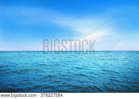 Blue Under Water Waves And Bubbles. Beautiful White Clouds On Blue Sky Over Calm Sea With Sunlight R