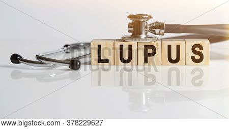 Lupus The Word On Wooden Cubes, Cubes Stand On A Reflective White Surface, On Cubes - A Stethoscope.